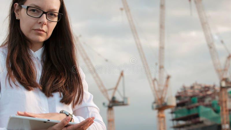El arquitecto en el emplazamiento de la obra hace la supervisión Ingeniero de sexo femenino joven con la tableta a disposición foto de archivo