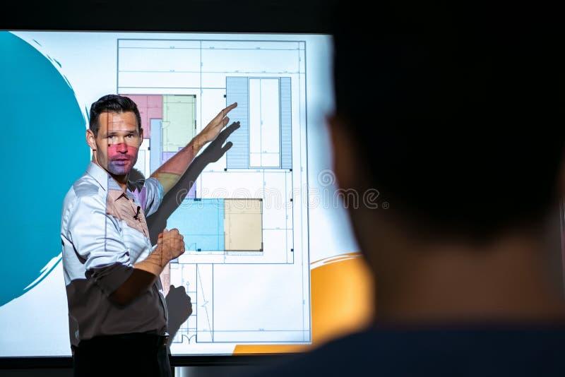 El arquitecto Talking And Projecting resbala en la reunión de negocios en oficina fotos de archivo
