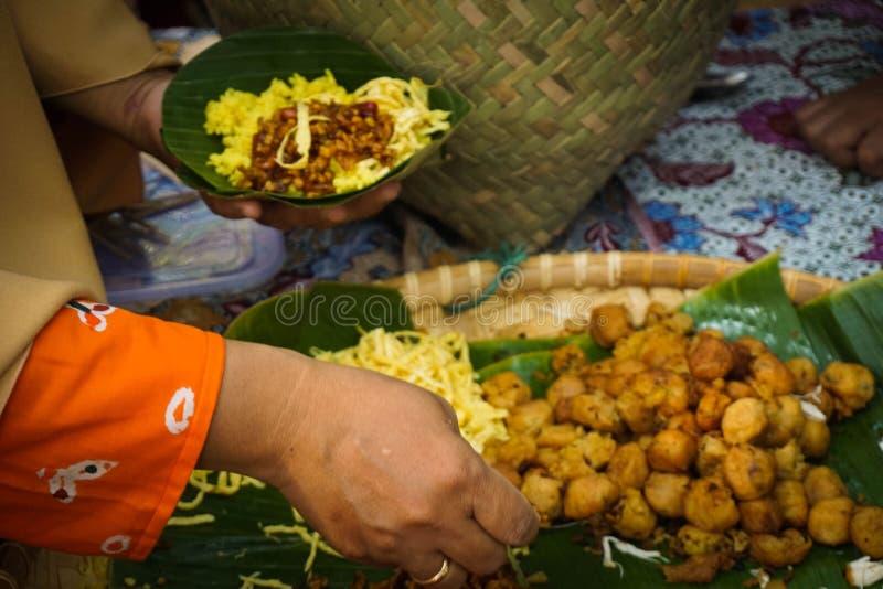 El arroz amarillo sirvió al vendedor que desempeñaba servicios en la placa de la hoja del plátano tradicional de Java central imagenes de archivo