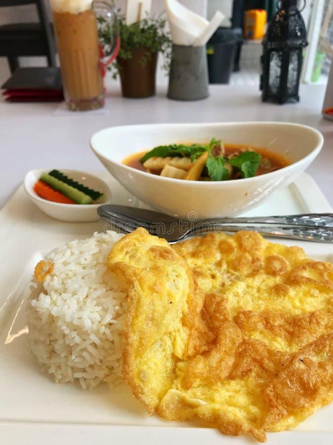 El arroz del jazmín con la tortilla en el top en la placa blanca con los chiles rojos calientes fortalece la sopa fotografía de archivo libre de regalías
