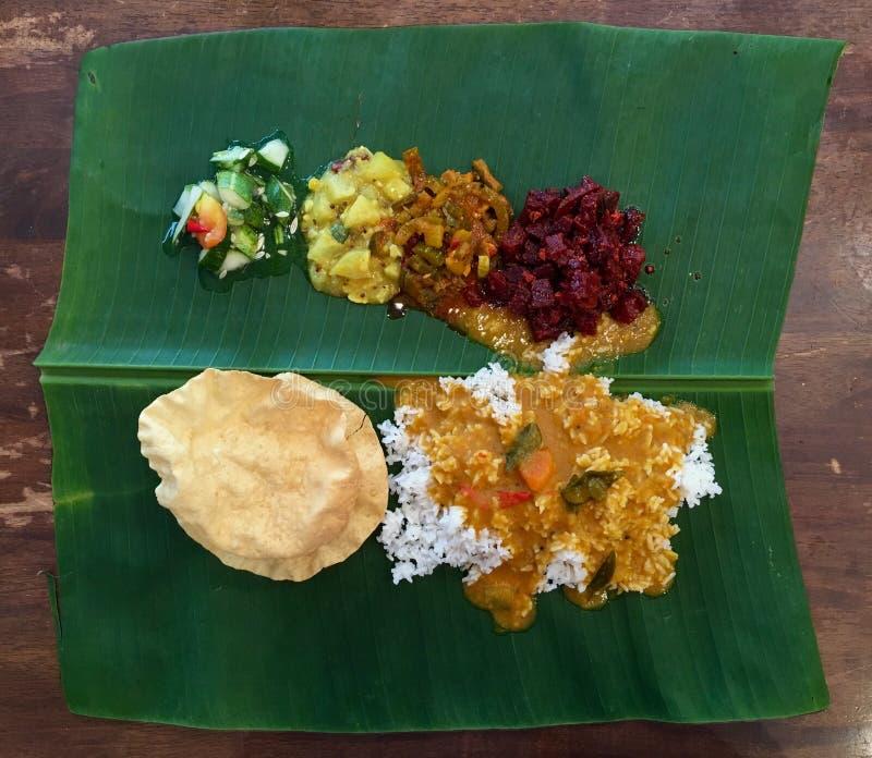 El arroz indio con la variedad de platos de las verduras sirvió en la hoja grande fresca del plátano imagen de archivo