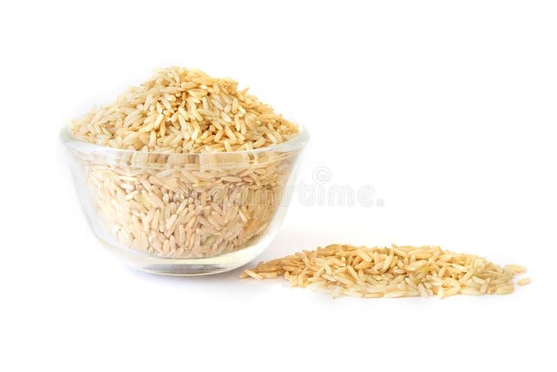 El arroz moreno en bol de vidrio en el fondo blanco, comida sana imagenes de archivo