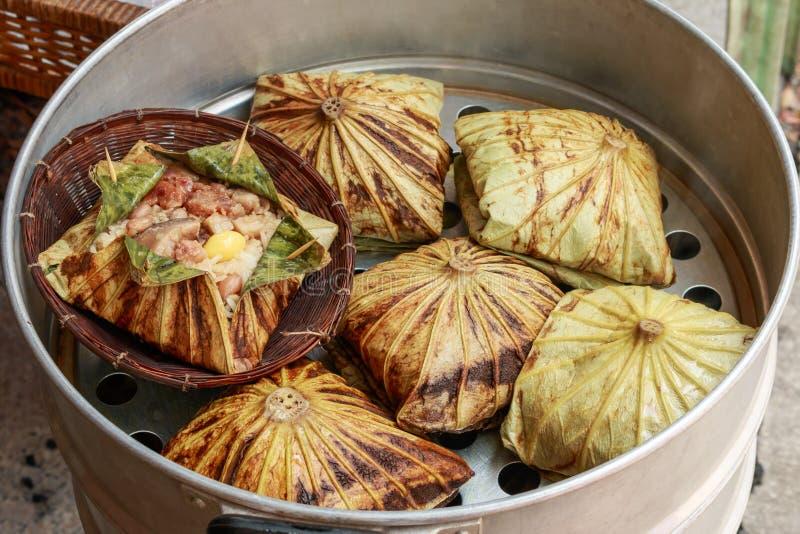 El arroz pegajoso envuelto en hoja o Zongzi del loto es chino tradicional que la comida se hace con arroz pegajoso imagenes de archivo