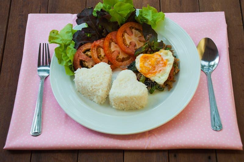 El arroz remató con cerdo y albahaca sofritos con el huevo imagenes de archivo