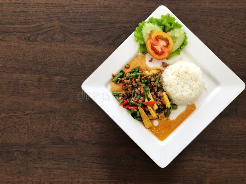 El arroz remató con el cerdo y la albahaca y la verdura sofritos, tomate en el plato blanco en la tabla negra foto de archivo