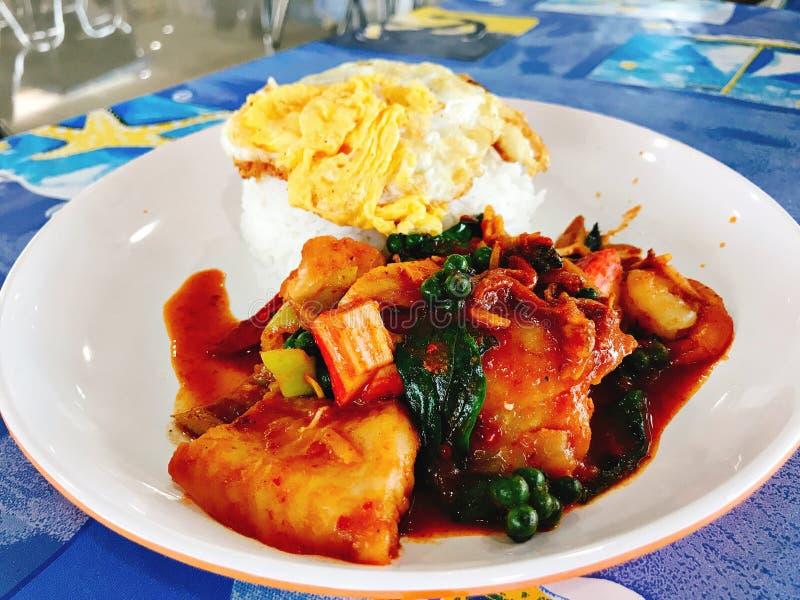 El arroz remató con el huevo frito, mariscos sofritos picantes con goma roja del curry fotografía de archivo