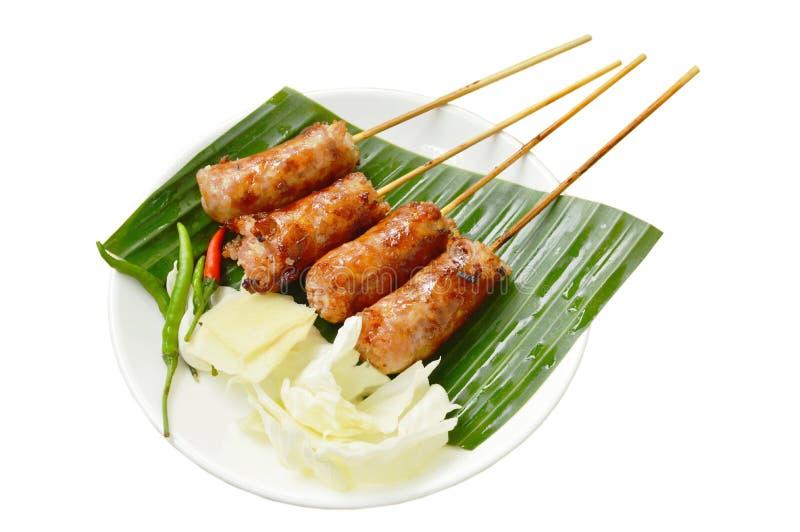 El arroz y el cerdo rellenos salchicha tailandesa asados a la parrilla comen con la verdura en la placa fotografía de archivo