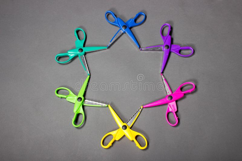 El arte brillantemente coloreado scissors la colocación en un fondo gris en la forma de una estrella imágenes de archivo libres de regalías