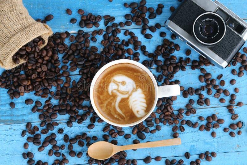 El arte del latte del café con el modelo el loro en tazas y un café sea imagenes de archivo