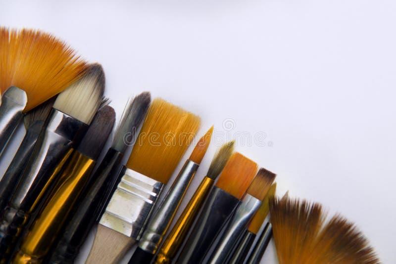 El arte limpio coloreó cepillos con blanco, negro y las cerdas anaranjadas se cierran encima de mentira en una hoja blanca de la  imágenes de archivo libres de regalías