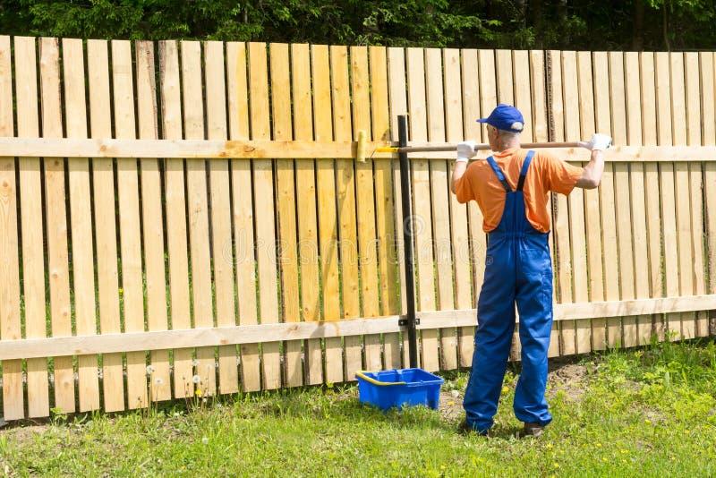 El artesano aplica la pintura en la pared en el jardín usando el rollo de la pintura fotos de archivo