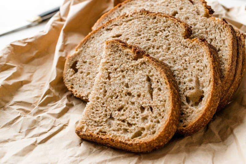 El artesano cortó rebanadas hechas en casa del pan de pan amargo con la bolsa de papel/el paquete o el papel del arte fotos de archivo