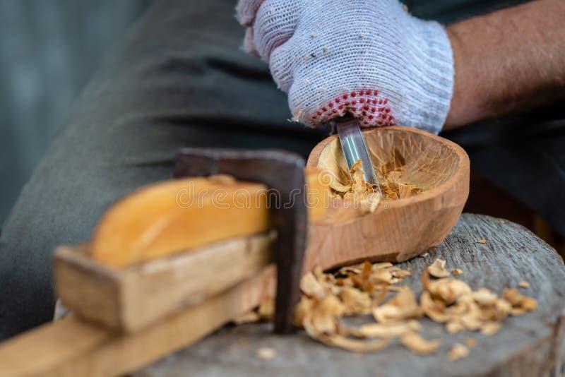 El artesano demuestra el proceso de hacer las cucharas de madera hechas a mano usando las herramientas El nacional hace concepto  fotos de archivo
