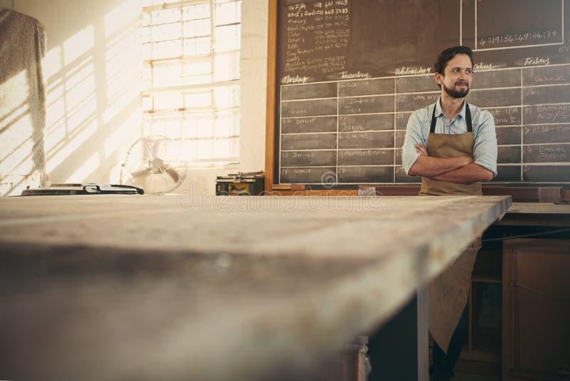El artesano en su taller que mira lejos con los brazos cruzados confía imagen de archivo