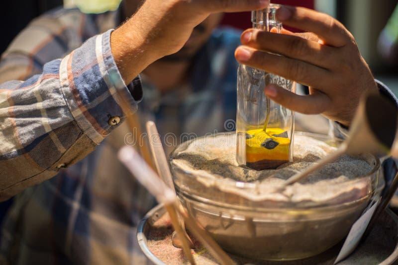 El artesano hace recuerdos en una botella usando la arena coloreada imagen de archivo libre de regalías