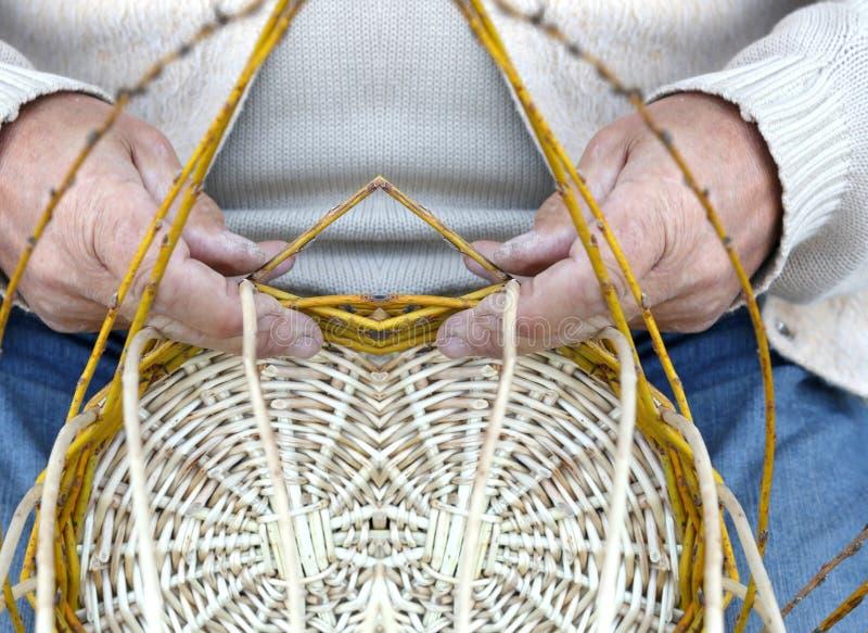 El artesano mayor crea una cesta de mimbre tejida foto de archivo