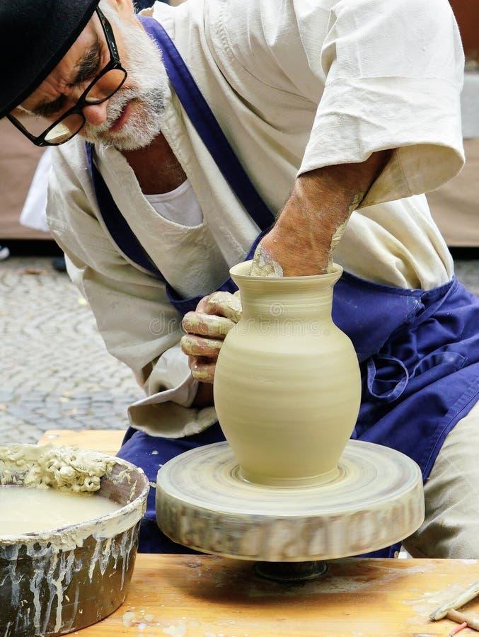 El artesano mayor hace girar la cerámica en su rueda en la feria del arte en Bratislava imagenes de archivo