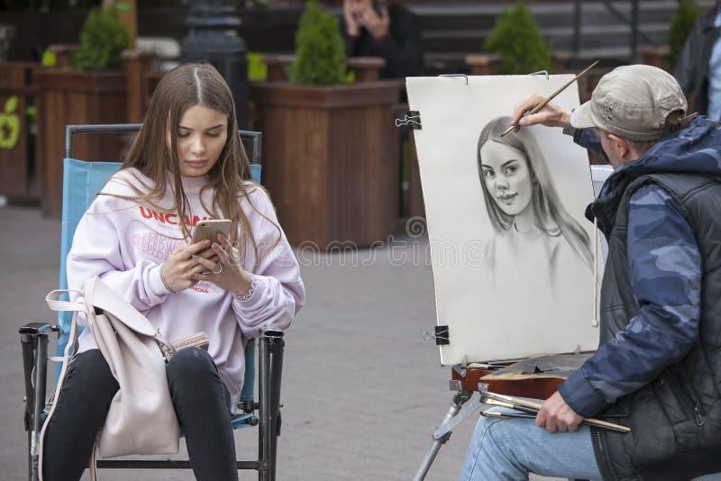 El artista de la calle pinta el retrato de una chica joven en las calles de Moscú fotografía de archivo