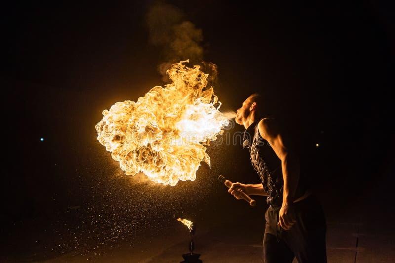 El artista de la demostración del fuego respira el fuego en la oscuridad imagen de archivo libre de regalías