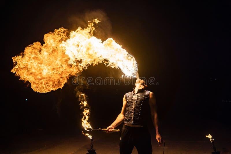 El artista de la demostración del fuego respira el fuego en la oscuridad fotografía de archivo