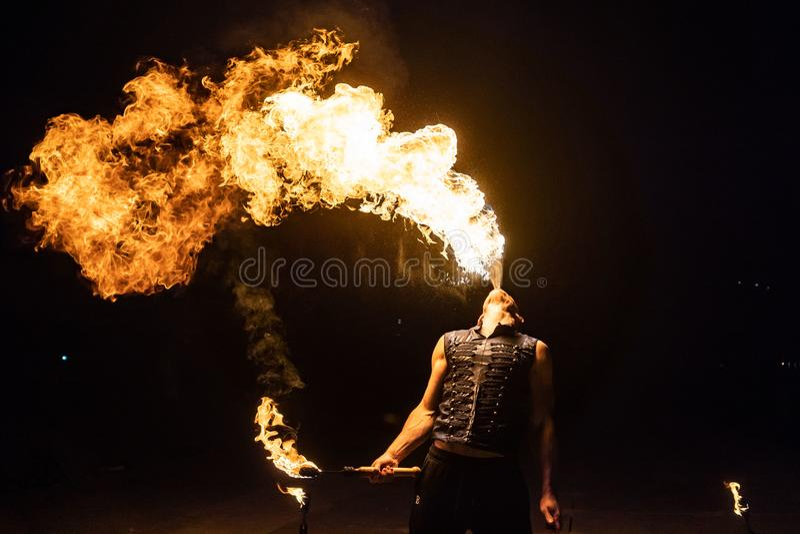 El artista de la demostración del fuego respira el fuego en la oscuridad foto de archivo