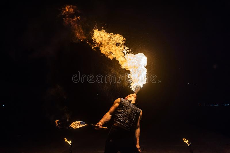 El artista de la demostración del fuego respira el fuego en la oscuridad imagenes de archivo