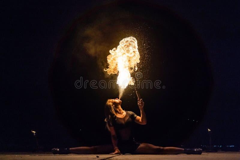 El artista de la demostración del fuego respira el fuego en la oscuridad imagen de archivo