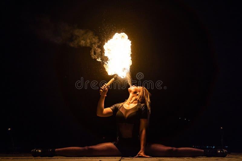 El artista de la demostración del fuego respira el fuego en la oscuridad fotos de archivo