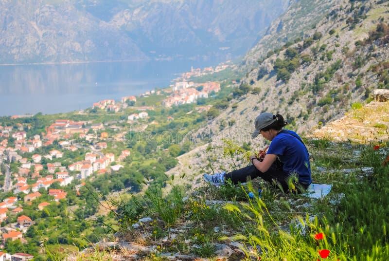 El artista de la muchacha pinta un paisaje en la montaña en la ciudad de Kotor foto de archivo libre de regalías