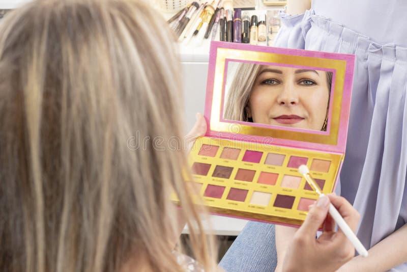 El artista de maquillaje aplica maquillaje al modelo el artista de maquillaje mira en un espejo de la paleta imagen de archivo libre de regalías