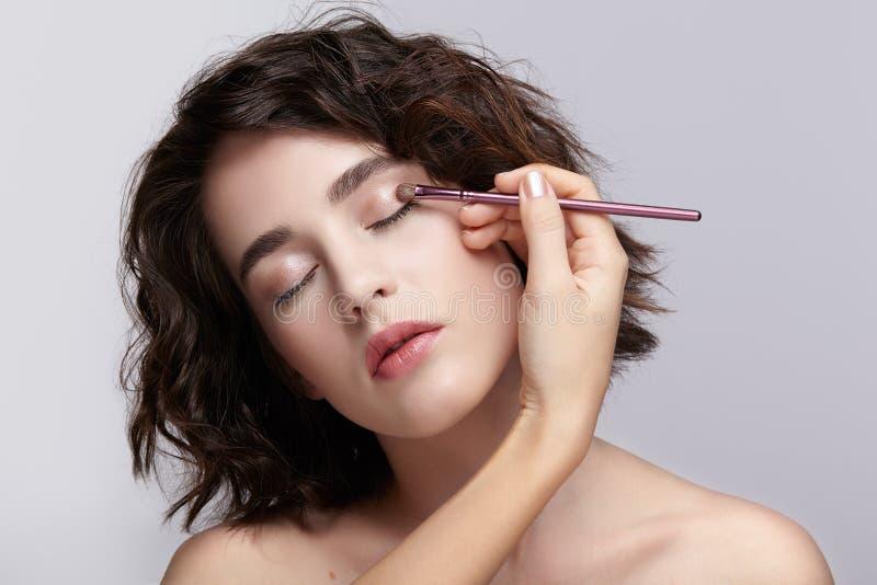 El artista de maquillaje aplica maquillaje de la belleza en los párpados de un hermoso imagen de archivo