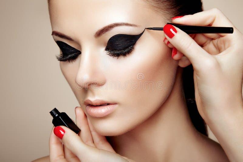 El artista de maquillaje aplica la sombra de ojo fotografía de archivo