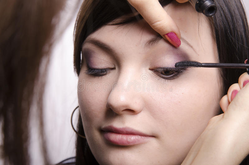 El artista de maquillaje en curso de maquillaje colorea el modelo de las pestañas fotos de archivo