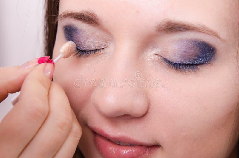 El artista de maquillaje es modelo sombreado de los párpados imagen de archivo libre de regalías