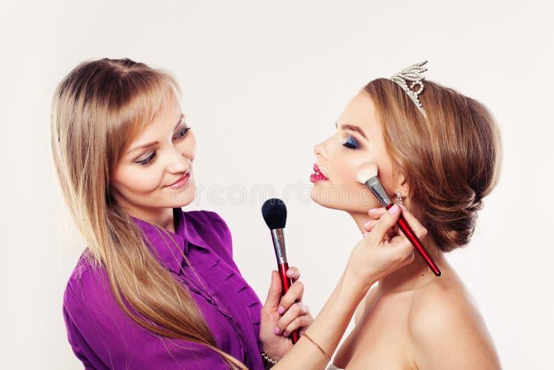 El artista de maquillaje Girl Applying Powder y se ruboriza imagenes de archivo
