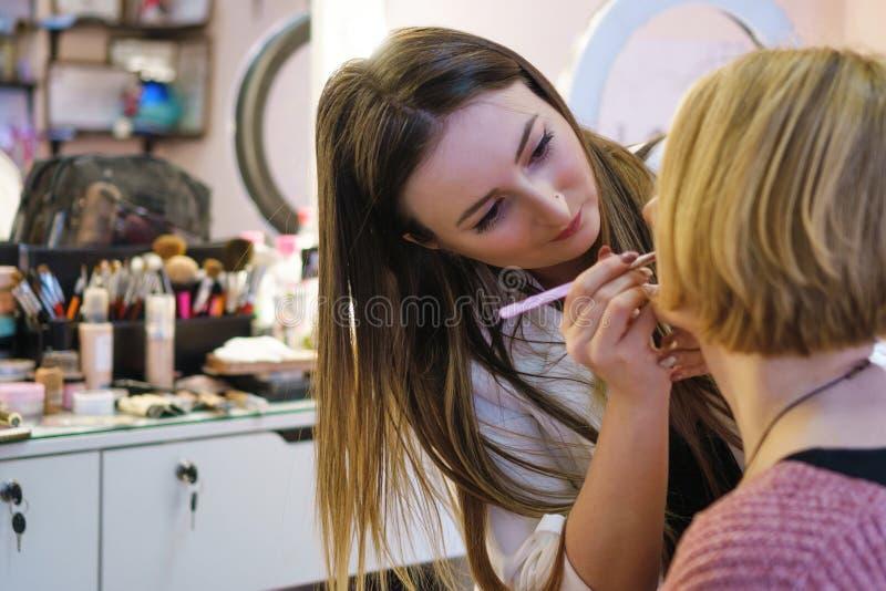 El artista de maquillaje hace maquillaje a la muchacha foto de archivo