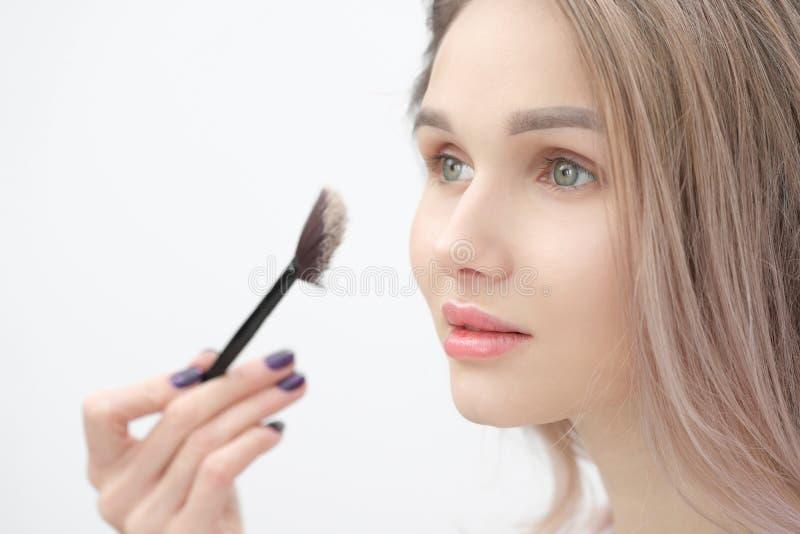 El artista de maquillaje hace maquillaje a la muchacha rubia hermosa en un fondo blanco Manos del primer con el cepillo y la cara imagenes de archivo