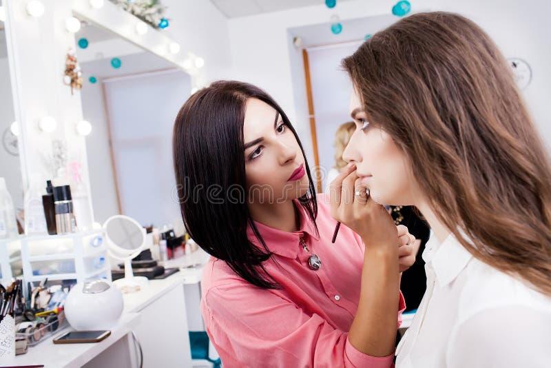 El artista de maquillaje hace maquillaje a una muchacha hermosa en un salón de belleza imágenes de archivo libres de regalías