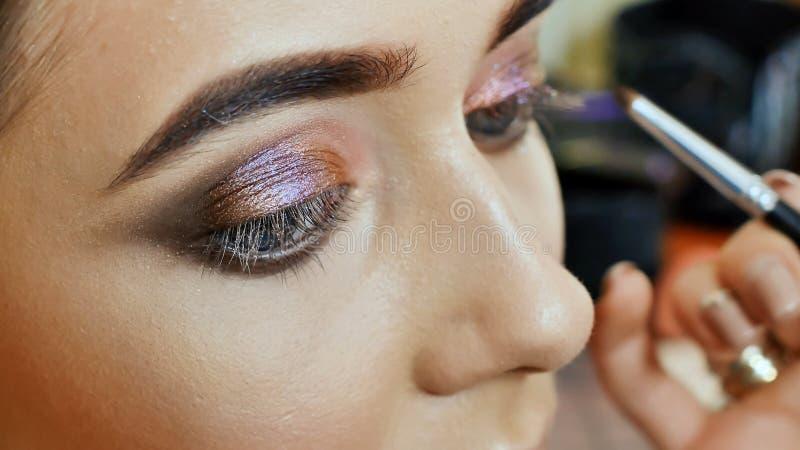 El artista de maquillaje de la muchacha pinta los ojos del modelo de la muchacha Movimiento de párpados superiores imágenes de archivo libres de regalías