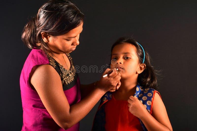 El artista de maquillaje de la mujer hace el maquillaje a una niña, Pune, maharashtra foto de archivo libre de regalías