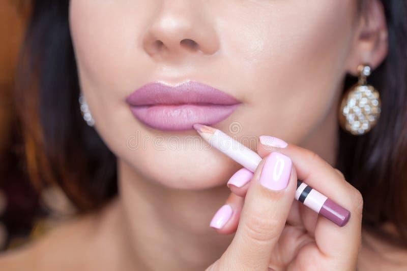 El artista de maquillaje pinta los labios de una mujer hermosa con un lápiz, termina el maquillaje del ` s del día fotos de archivo