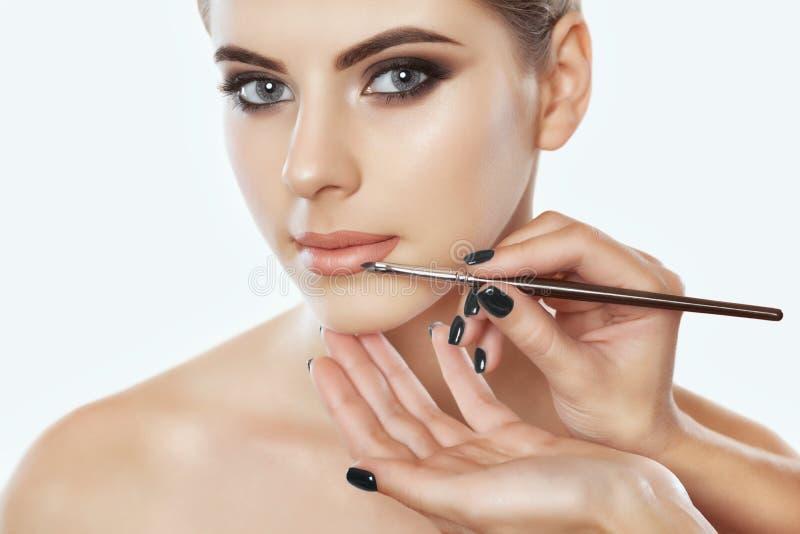 El artista de maquillaje pinta los labios de una mujer hermosa, termina el maquillaje del día foto de archivo