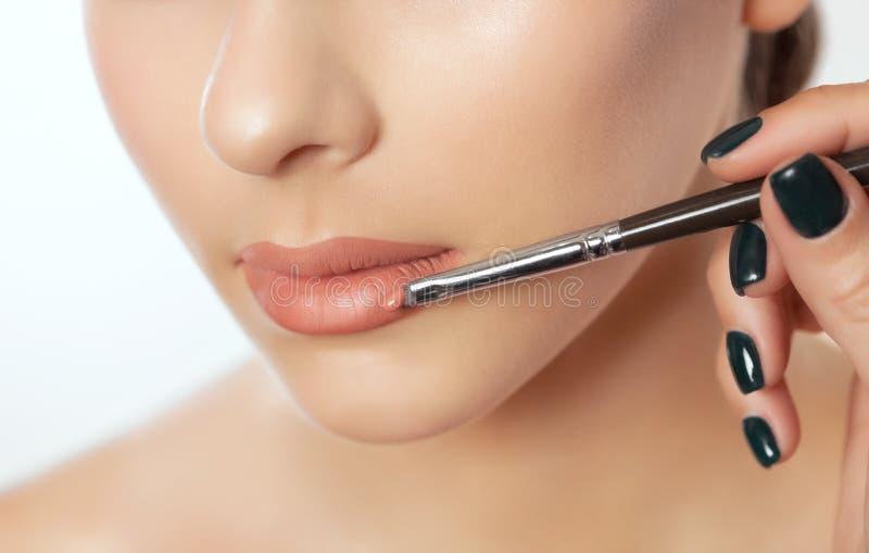 El artista de maquillaje pinta los labios de una mujer hermosa, termina el maquillaje del día imágenes de archivo libres de regalías
