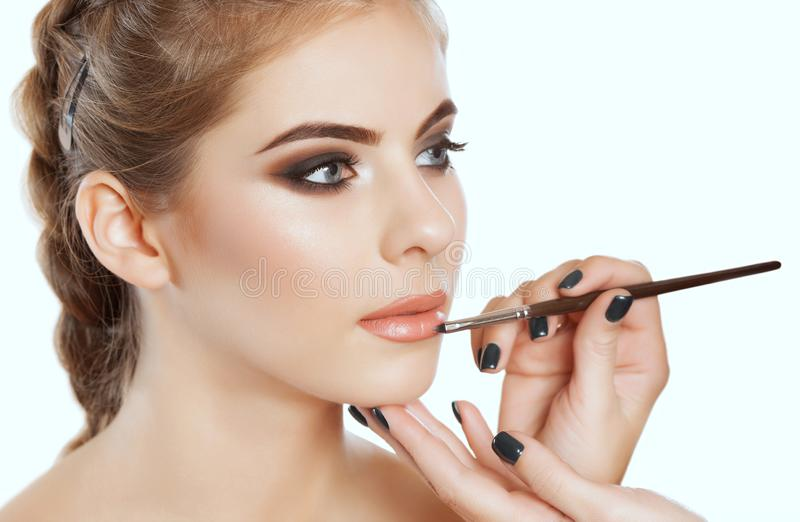 El artista de maquillaje pinta los labios de una mujer hermosa, termina el maquillaje del día en el salón de belleza fotografía de archivo