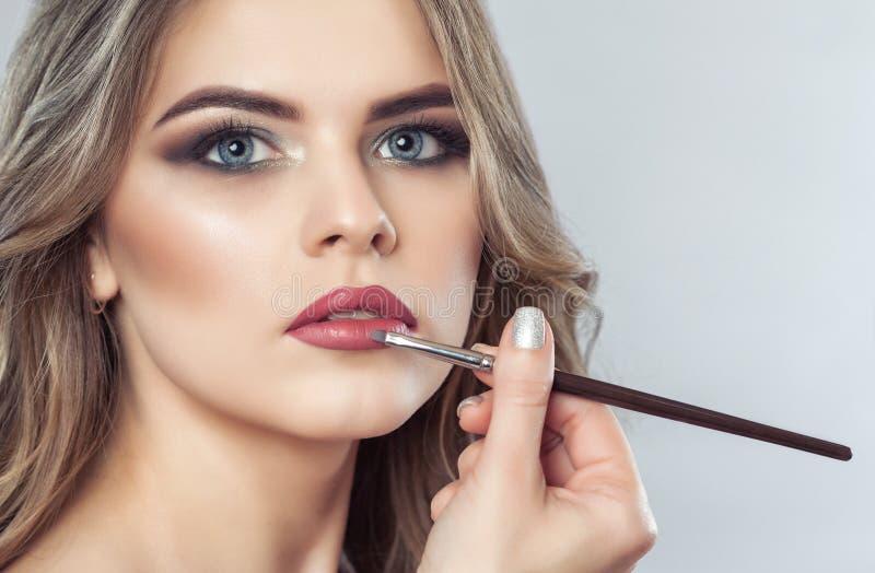 El artista de maquillaje pinta los labios de una mujer hermosa, termina el maquillaje del día imagen de archivo