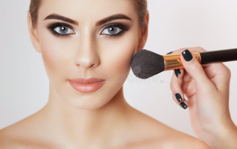 El artista de maquillaje pinta el polvo en la cara de la muchacha, termina el maquillaje del día fotografía de archivo libre de regalías