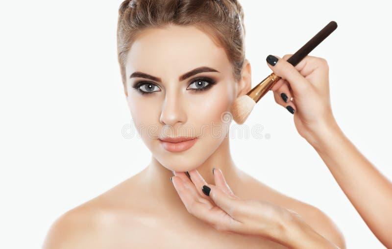 El artista de maquillaje pinta el polvo en la cara de la muchacha, termina el maquillaje del día foto de archivo libre de regalías