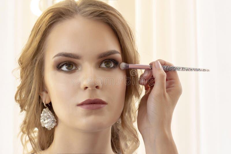El artista de maquillaje pone maquillaje en modelo de la muchacha El cepillo aplica las sombras, lápiz corrector retrato modelo d fotografía de archivo