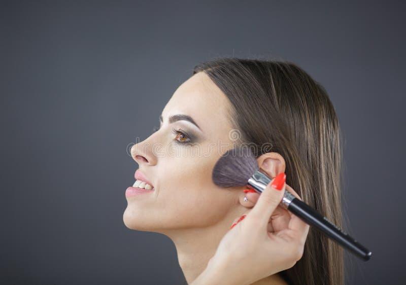 El artista de maquillaje puso la ruborización en la cara del ` s de la muchacha foto de archivo