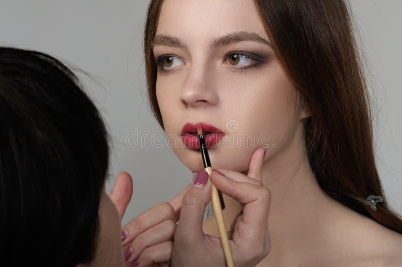 El artista de maquillaje teñe los labios del modelo antes de tirar con foto de archivo